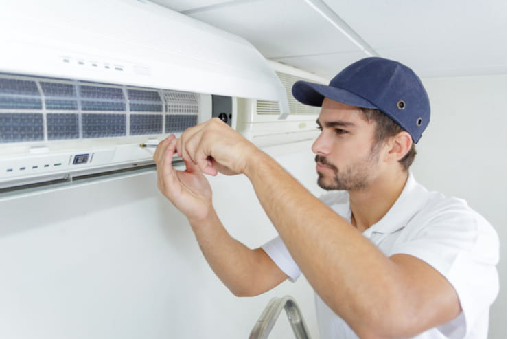Worker assembling Air Conditioning unit